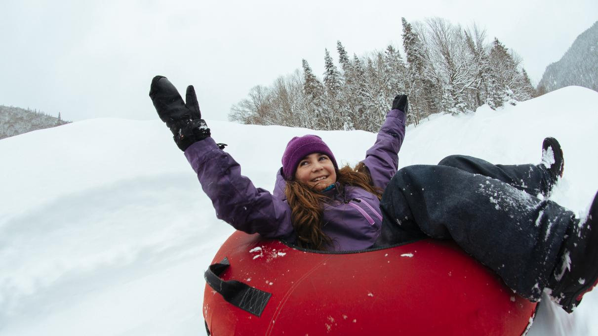 A young girl slides on an inner tube in winter, in the Jacques-Cartier National Park.