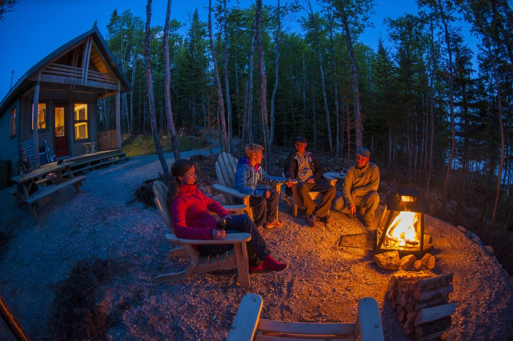 Friends around a campfire, outside, in front of a chalet in the Réserve faunique des Laurentides, in summer.
