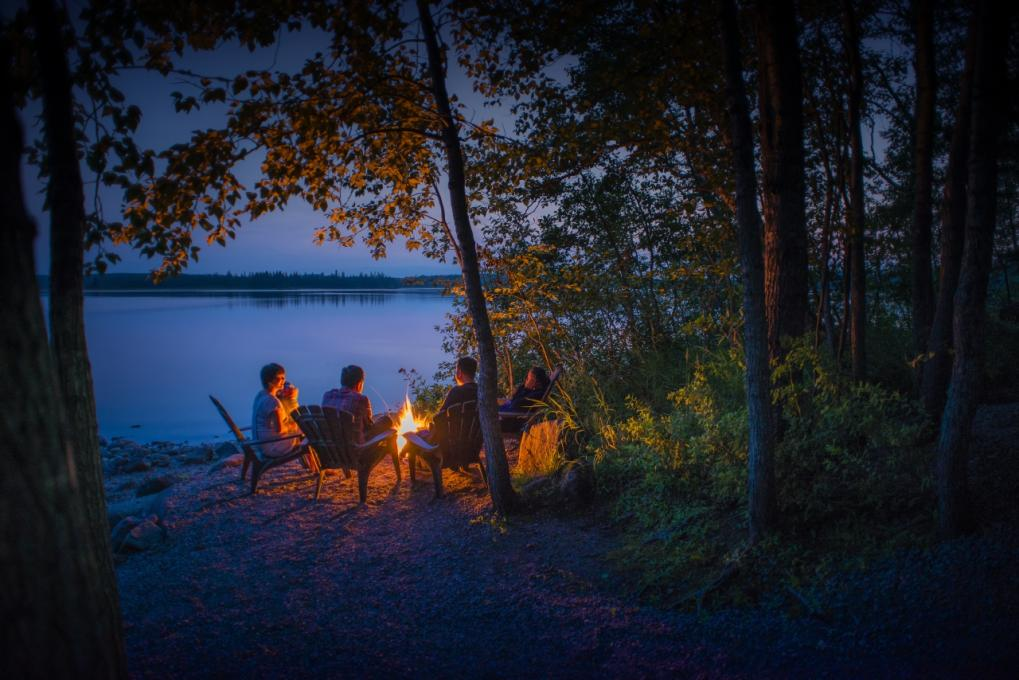 Friends around a campfire, near a lake in the Réserve faunique des Laurentides, in the early evening, in summer.