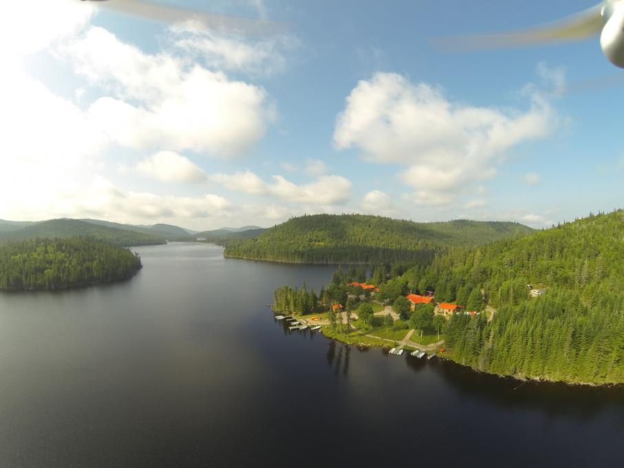 In the Réserve faunique des Laurentides, aerial view of the vastness of a lake in the middle of the forest and of several cabins with access to the lake, in summer.