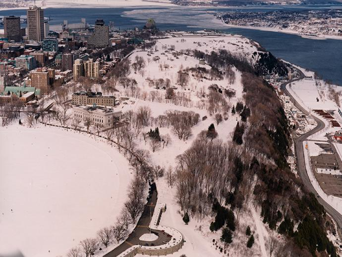 Aerial view of the Plains of Abraham in winter with Old Québec and the St. Lawrence River in the background.