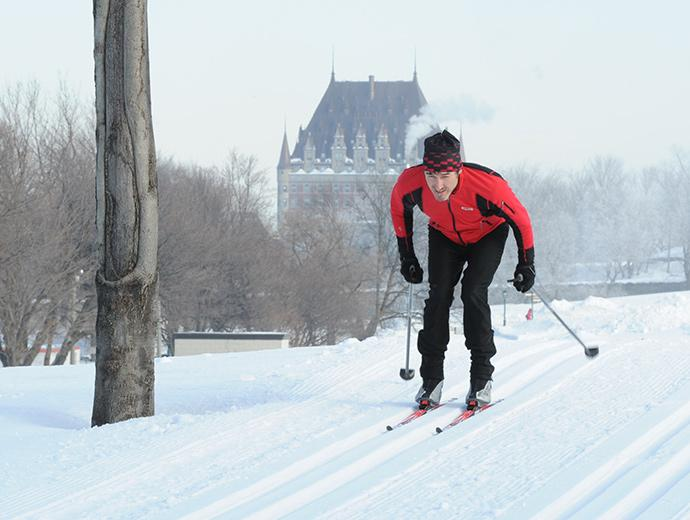 A man cross-country skiing on the Plains of Abraham with the Chateau Frontenac in the background.