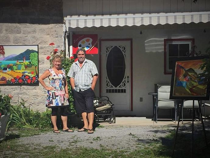 The artists Louise Marion and Yvon St-Aubin posing in front of their art gallery