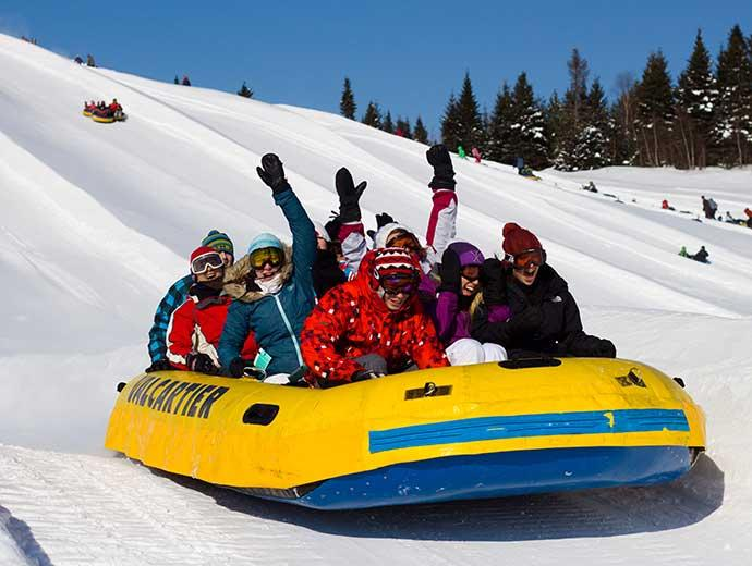 A group of people goes on a snow rafting descent at Village Vacances Valcartier, in winter.