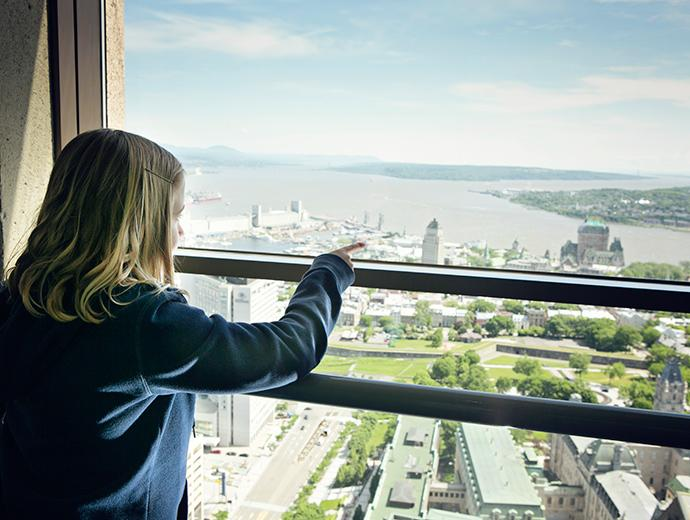 A young girl observes the view of Québec City from the Observatoire de la Capitale.