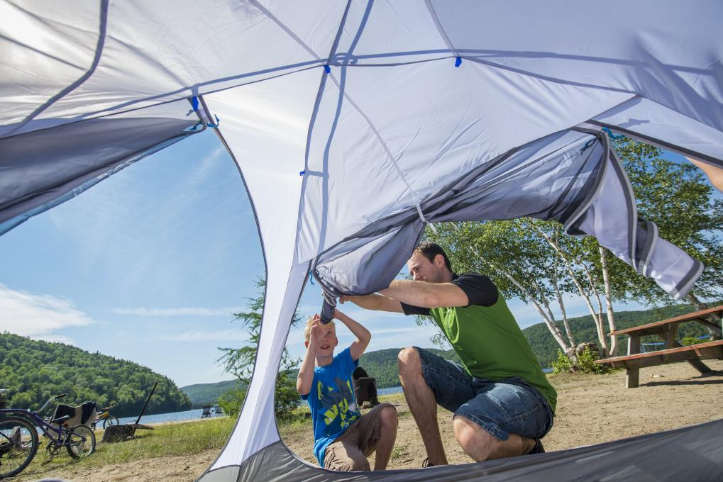 A father and his child set up a tent on a campsite near the water in the Portneuf Wildlife Reserve.