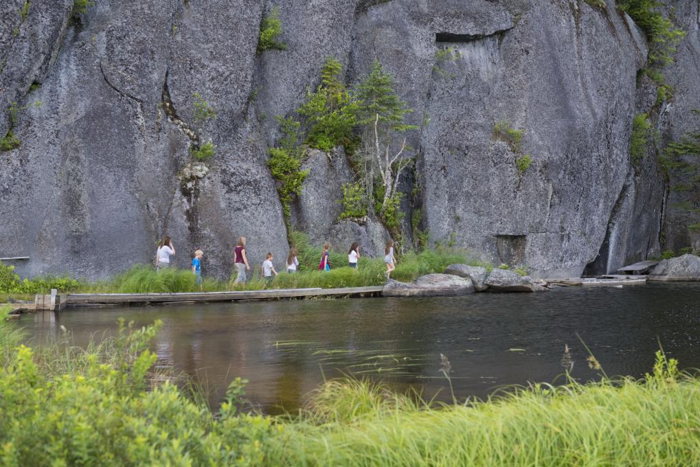 A group of people hikes near a cliff in the Portneuf Wildlife Reserve.