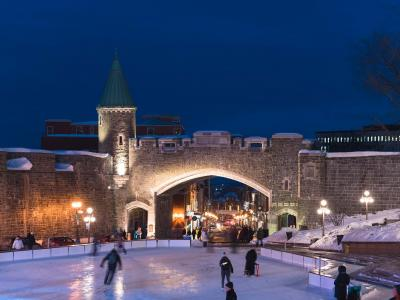 Porte Saint-Jean illuminated in the evening and skating at the Place D'Youville ice rink.