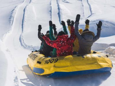 A group goes rafting on snow, arms in the air, in a slide at Village Vacances Valcartier.