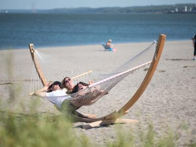A couple relaxes under the sun, in a hammock, on the beach at Baie de Beauport.