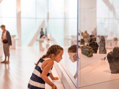 A young girl looks through a display case in an exhibition at the Musée national des beaux-arts du Québec.
