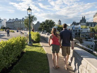 A couple walk hand in hand in summer on the Pierre-Dugua-De Mons terrace.