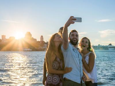 Friends taking a picture at sunset, near the St. Lawrence River in Lévis with a panorama of Old Québec in the background.