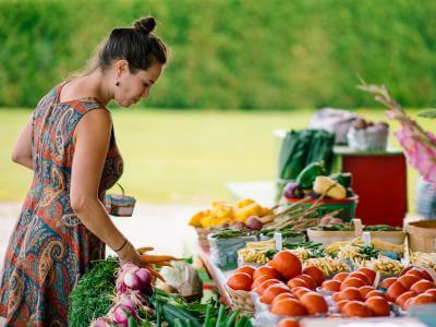 A woman buys fresh fruits and vegetables from an outdoor kiosk.