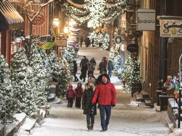 Several people walk in the evening on rue du Petit-Champlain, covered with snow and decorated with many illuminated trees.