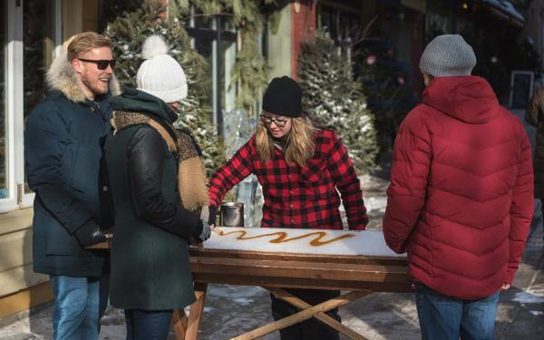 Three people stop in the Petit-Champlain district to taste taffy on snow in a small sugar shack.