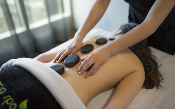 A woman receiving a hot stone massage at the Aroma Spa at Village Vacances Valcartier.