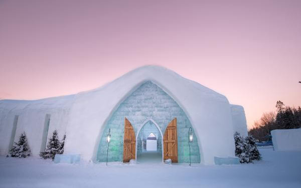 Exterior facade of the Hôtel de Glace and a pink sky, in Saint-Gabriel-de-Valcartier, near Québec.