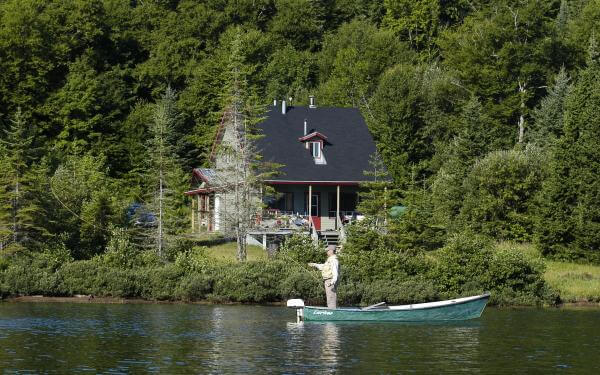 A house by the water and a fisherman in a rowboat in the Portneuf Wildlife Reserve.