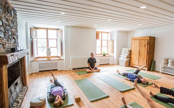 Several people participate in a yoga class at the Monastère des Augustines.