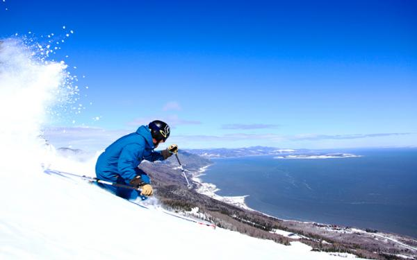 An alpine skier at the top of a mountain in the Massif de Charlevoix with a view of the St. Lawrence River.