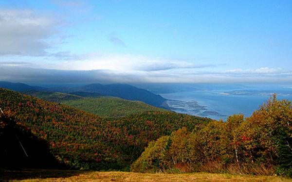 Fall colors and the St. Lawrence River seen from the top of a mountain in the Massif de Charlevoix.