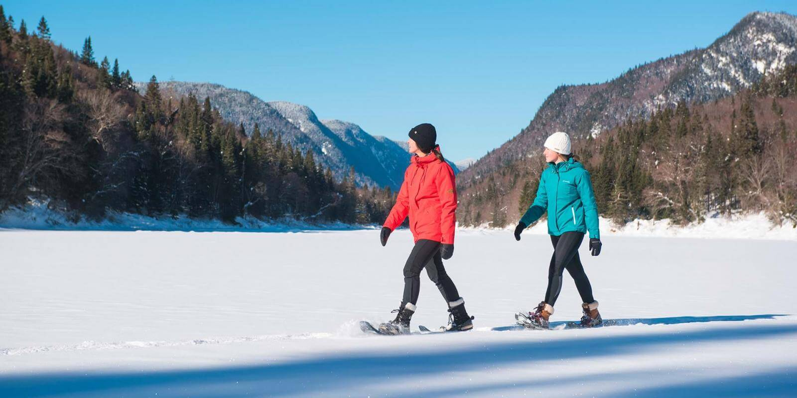 Two girls on snowshoes enjoy a sunny winter day in Jacques-Cartier National Park.