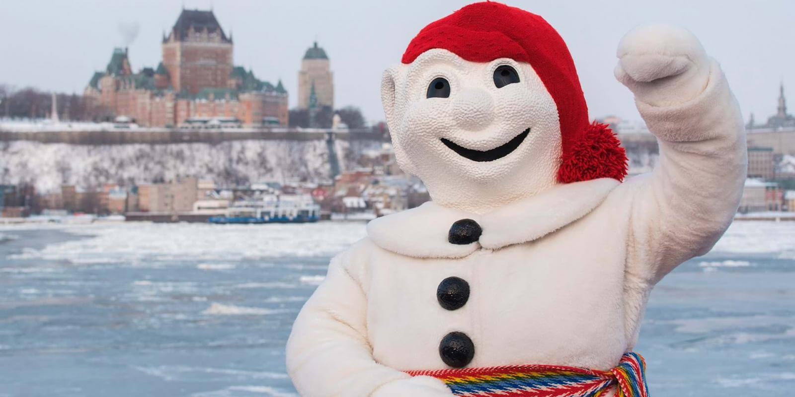 Bonhomme Carnaval proudly poses in front of the Château Frontenac, aboard the Québec-Lévis Ferry.