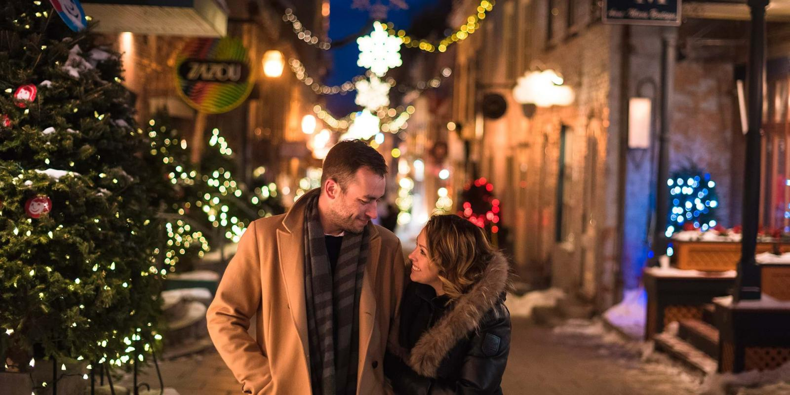 A couple in love walks in the evening in the rue du Petit-Champlain illuminated for Christmas and the holidays.