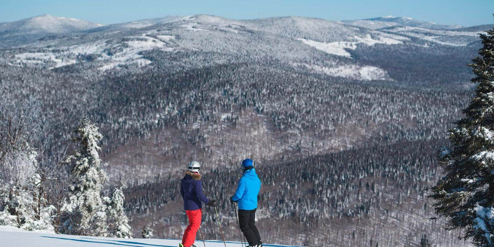 Two skiers observe the snow-capped mountains at the top of the Mont-Sainte-Anne alpine ski resort.