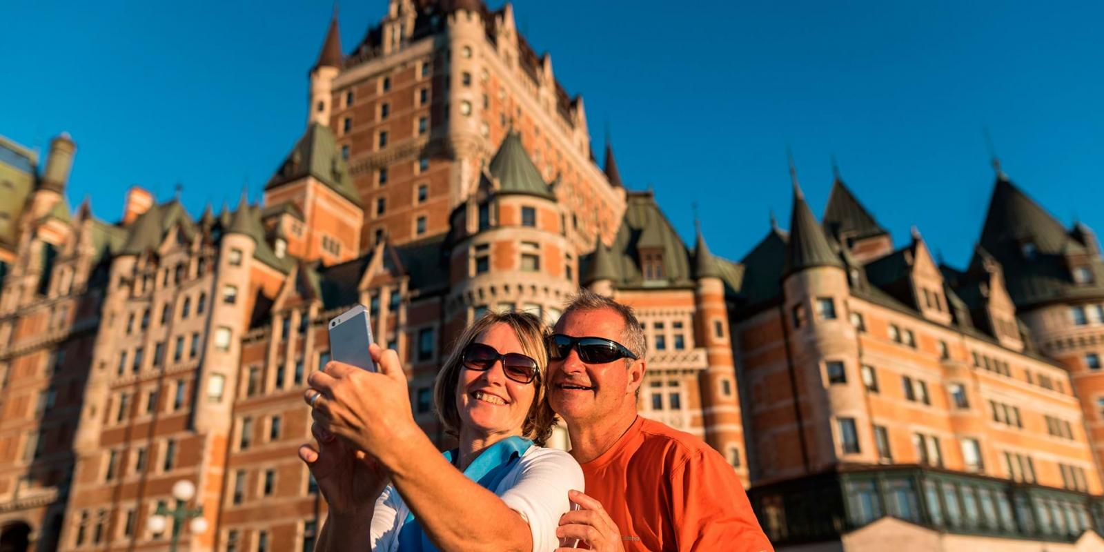 A couple takes a picture of themselves on the Dufferin terrace, in front of the Château Frontenac.