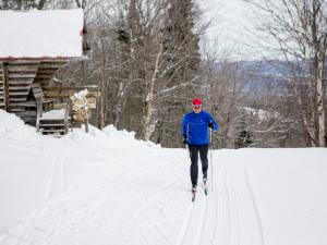 A man is cross-country skiing on the trails at Mont-Sainte-Anne.