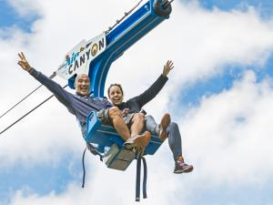Two people in the air, seated in the AirCanyon duo at Canyon Sainte-Anne.