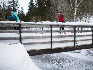 Two people cross-country skiing at Mont-Sainte-Anne, crossing a bridge over a river.