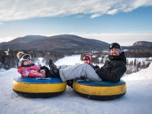 A family is getting ready to slide on inner tubes at Village Vacances Valcartier in winter.