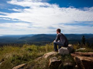A man sits and observes the panorama on the La Crête trail at Mont-Sainte-Anne.