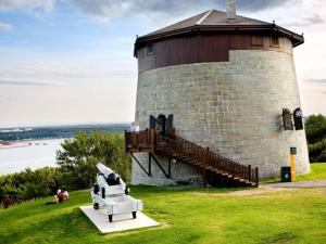 Commission des champs de bataille nationaux - Martello Tower 1 on the Plains of Abraham and view of the St. Lawrence River in summer.