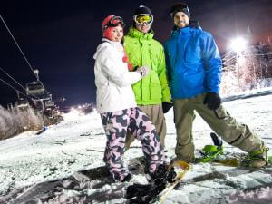 Three young snowboarders at Stoneham Ski Station in the evening.
