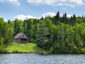 A chalet in the forest and on the edge of a lake in the Portneuf Wildlife Reserve.