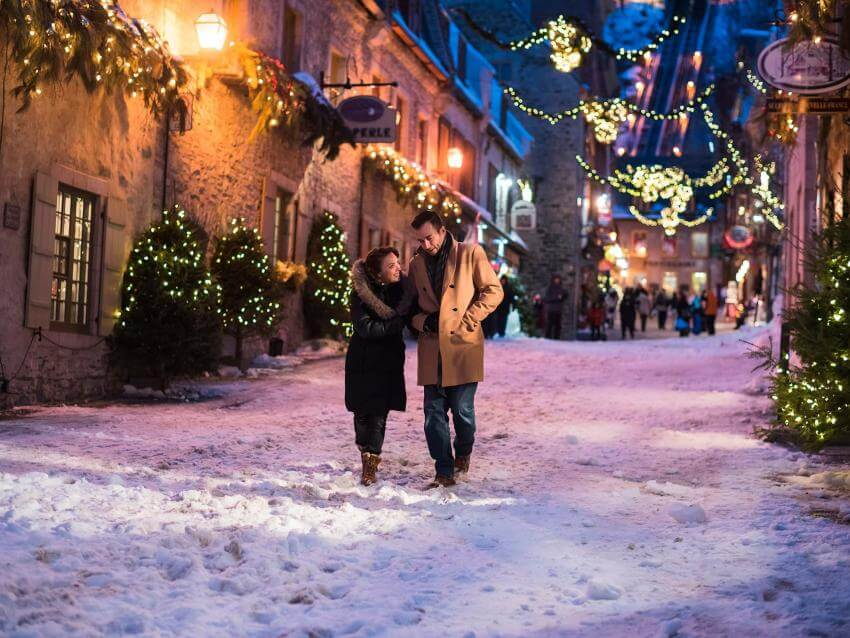 Couple walking in the snowy Sous-le-Fort street in the Petit-Champlain district, with the illuminated Christmas decorations.