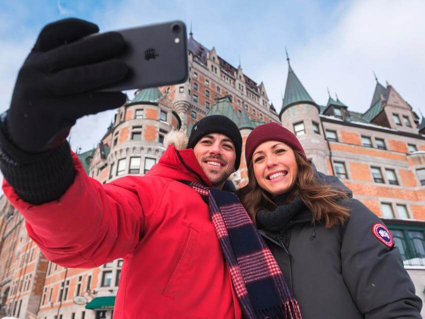 A smiling couple takes a picture of themselves in front of the Château Frontenac, in winter.