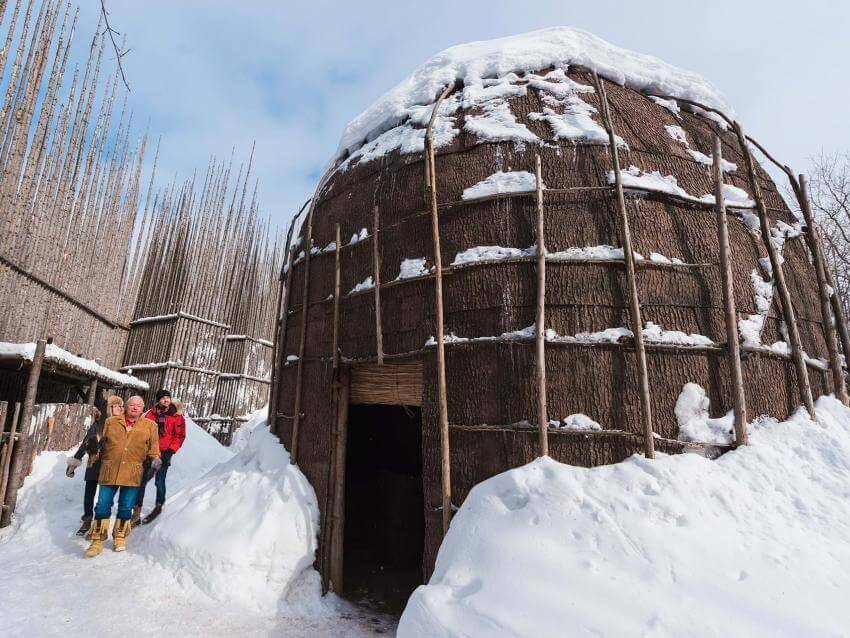 A couple walks outside the snowy longhouse with a guide, in Wendake near Québec City.