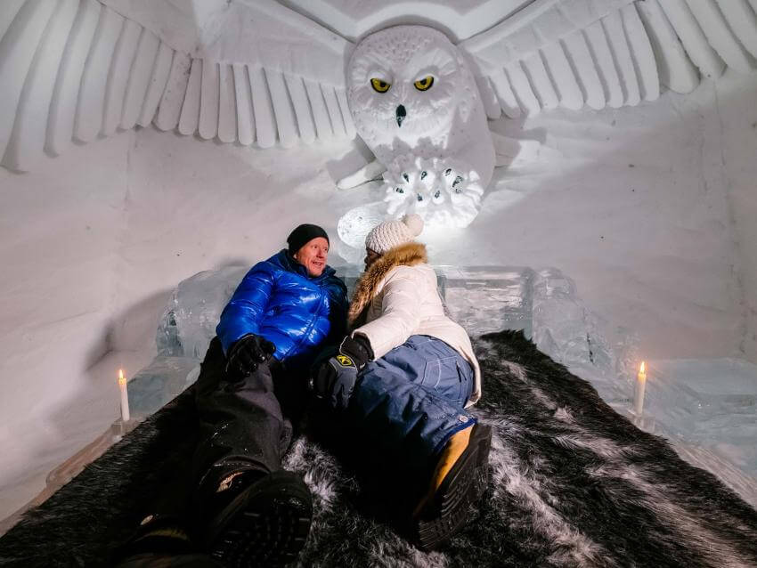 Couple on a bed in a room of the Ice Hotel