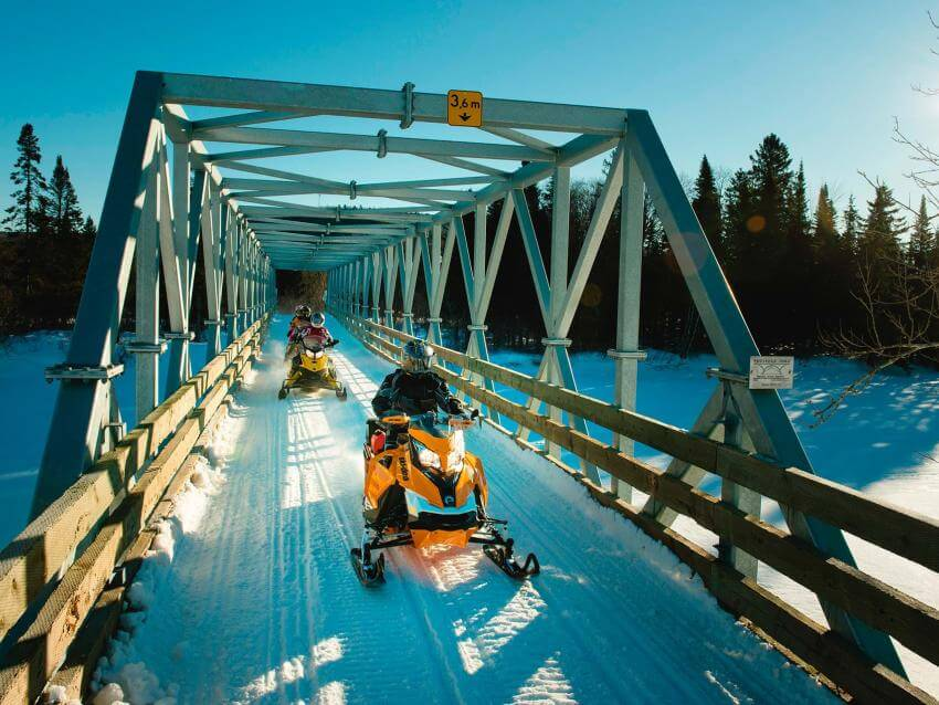 Snowmobiles crossing a bridge in Portneuf