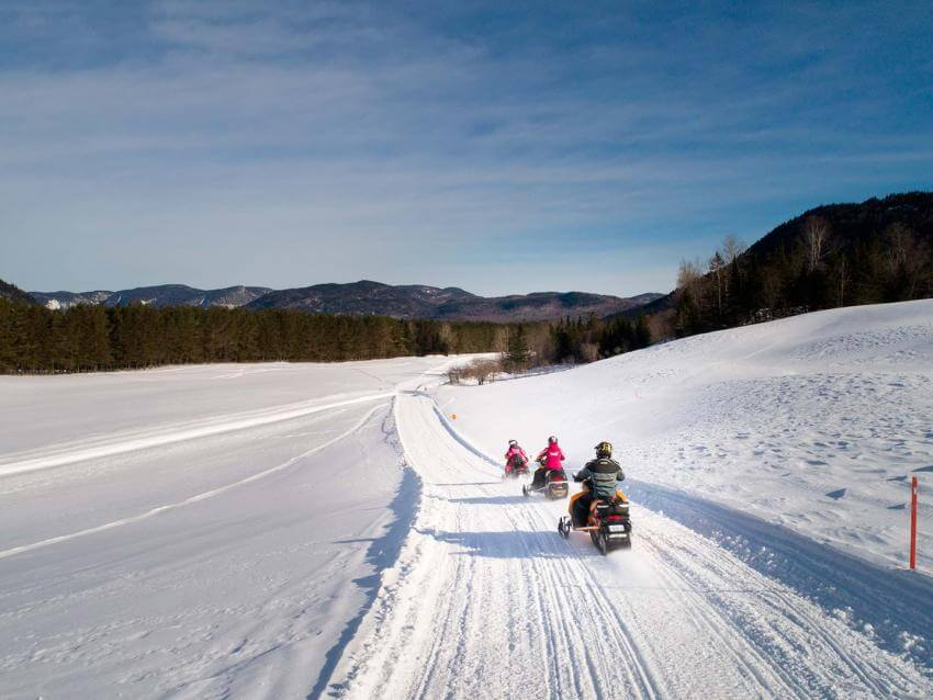 Snowmobilers riding in a field