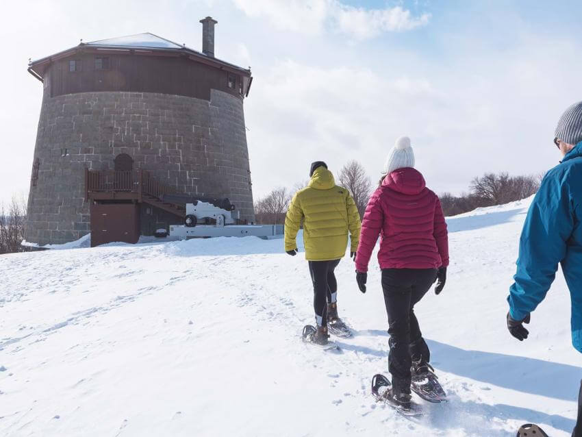 Three snowshoe hikers on the Plains of Abraham are heading towards Martello Tower no.1.