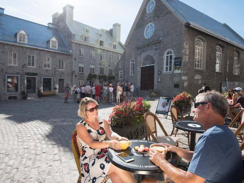 A couple drink a coffee next to Notre-Dame-des-Victoires Church, on the terrace of Maison Smith in Place Royale.