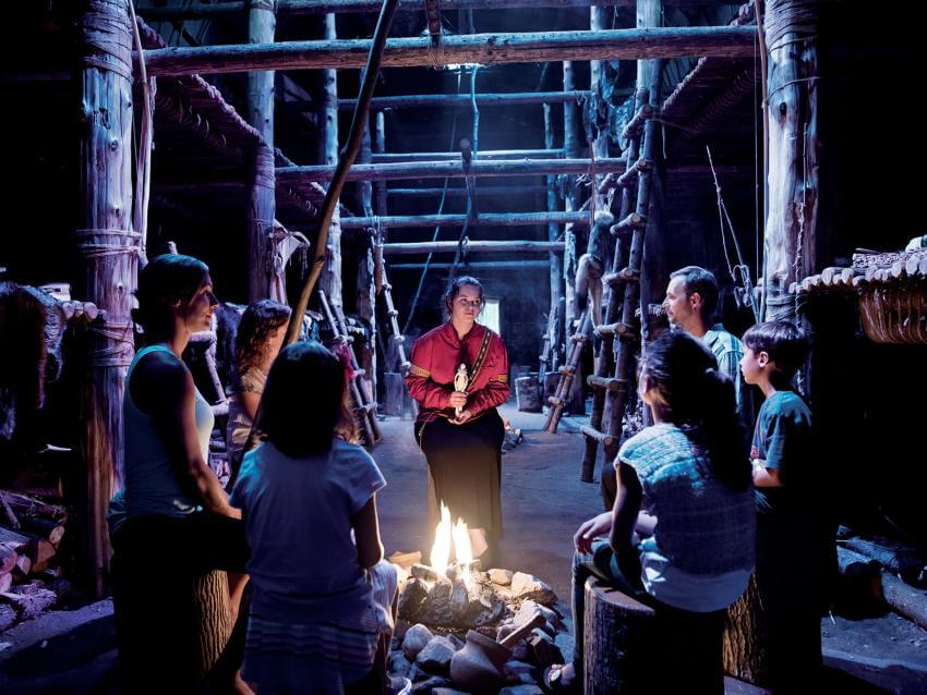Visitors around a fire listen attentively to an Amerindian legend told by a storyteller in the Wendake longhouse.