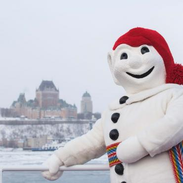 Bonhomme Carnaval is photographed on the exterior bridge of the Québec-Lévis Ferry, in winter.