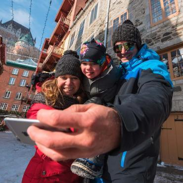 A family photograph themselves in the snowy Petit-Champlain district, with the Château Frontenac in the background.